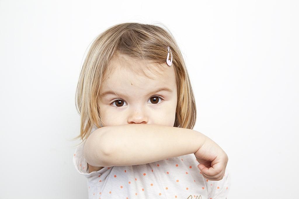 Enfant qui se couvre le visage avec sa mains contre le corona virus geste barrière en crèche